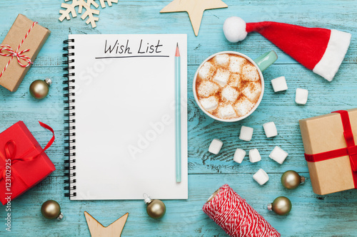 Photographie  Cup of hot cocoa or chocolate with marshmallow, holiday decorations and notebook with wish list on turquoise vintage table from above, christmas planning concept