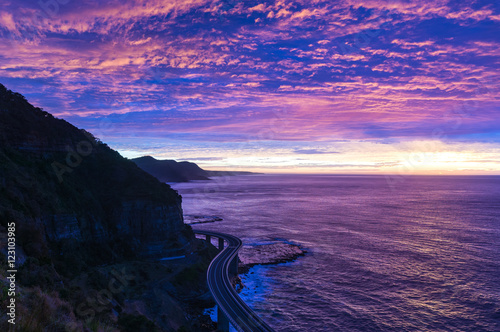 Foto op Aluminium Aubergine Sea Cliff Bridge on sunrise with beautiful pink and purple, violet sky and ocean shore on the background. The Bridge is part of Grand Pacific highway and is scenic route along coastal NSW, Australia