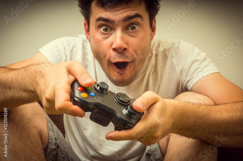 Photo  Emotional young addicted man playing video games