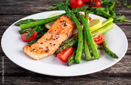 Foto  Fried salmon with asparagus, tomatoes, lemon, yellow lime on white plate