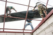 Roofing construction workers install metal sheet on the roof.