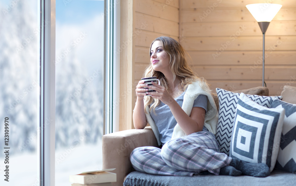 Fototapety, obrazy: Young beautiful blonde woman with cup of coffee sitting home in living room by the window. Winter snow landscape view. Lazy day off concept