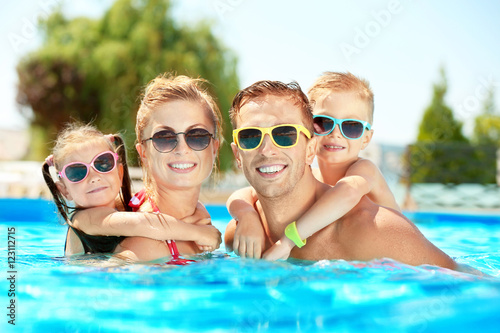 Fotografie, Obraz  Happy family in swimming pool at water park