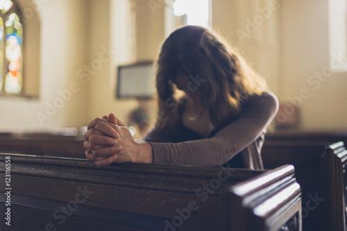 Obraz na płótnie Young woman praying in church