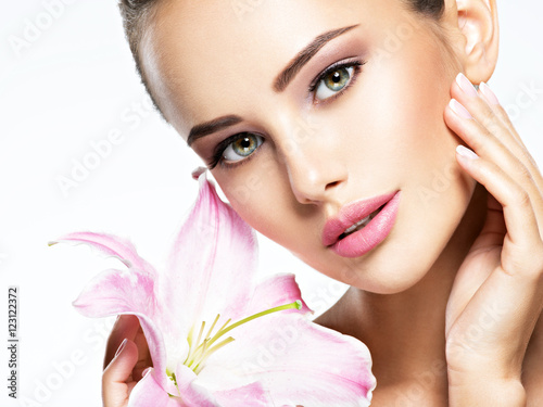 Beauty pure face of the young beautiful girl with flower