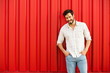 canvas print picture - attractive man smiling and standing o red wall