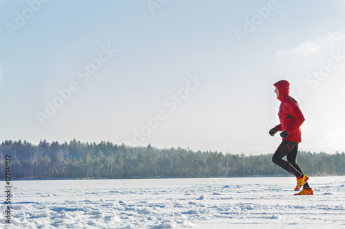 Poster Glisse hiver Trail racing runner wearing red protective sportswear on winter training session outdoors