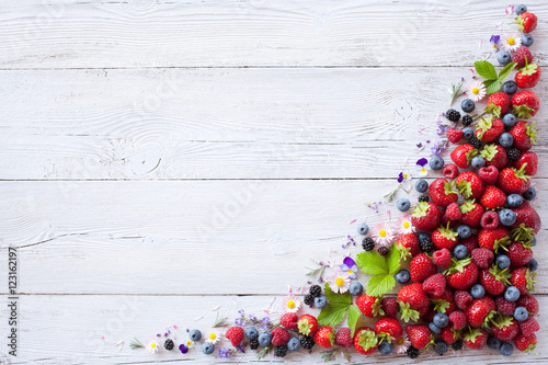 Photo  Wooden background with berries and flowers