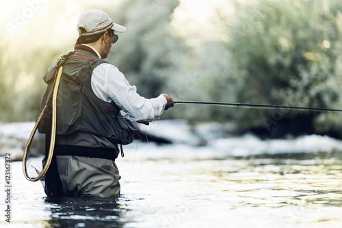 Fotografie, Obraz  Fly fisherman using flyfishing rod.