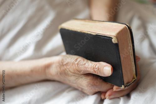 Photo Praying senior holds bible