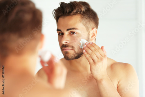 Young man shaving and looking into mirror