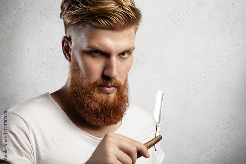 Fotografie, Obraz  Headshot of attractive professional barber with thick red beard and mustache, holding razor