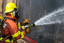 Firefighter Hold And Adjust Nozzle And Fire Hose Spraying Water