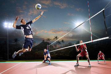 Fototapeta Professional volleyball players in action on the night court