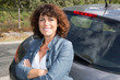 Attractive woman is standing near her car.
