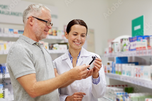 Tuinposter Apotheek pharmacist showing drug to senior man at pharmacy