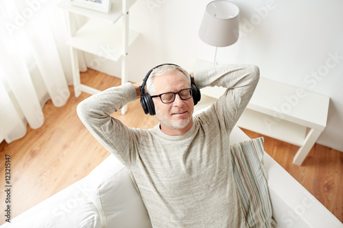 Photo  happy man in headphones listening to music at home