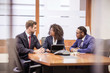 Young businesswoman and two businessmen brainstorming at boardroom table