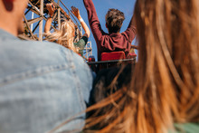 Friends On Roller Coaster Ride At Amusement Park
