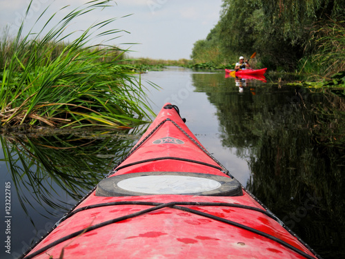 Nose of the red kayak on the background of wild nature. Kayaking