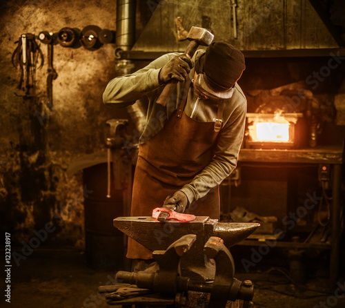Fotografia The blacksmith forging the molten metal on the anvil in smithy