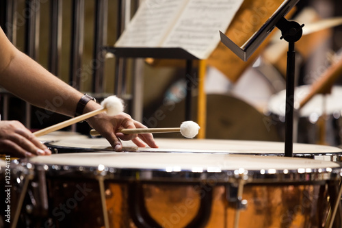 Fotografiet Hands musician playing the timpani in the orchestra closeup