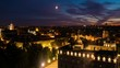 Sunset cloudy sky over Vilnius, Lithuania. Historical buildings. Time-lapse of the moving moon