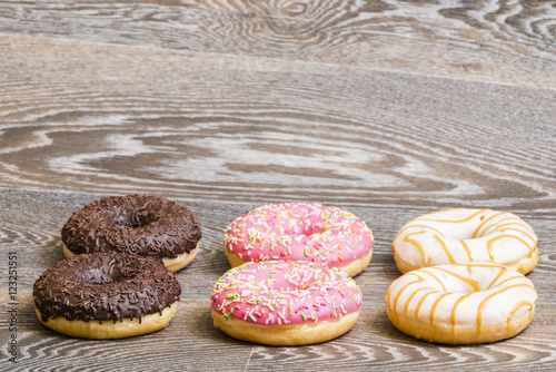 Photo  Hand decorated donuts on a wooden background