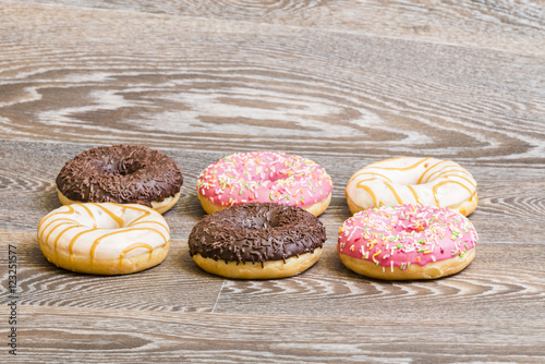 Photo  colorful donuts, isolated on a wooden background