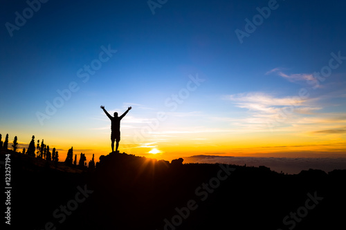 Man with arms outstretched celebrate mountains sunset Wallpaper Mural