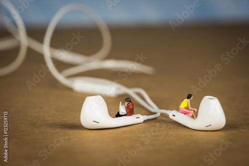 Fotografie, Obraz  Miniature Figures Sitting on Earbuds listening to Music