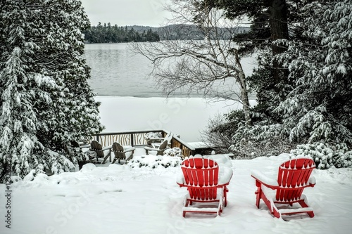 Valokuva  Pair of wooden adirondack chairs in the snow in front of the fro