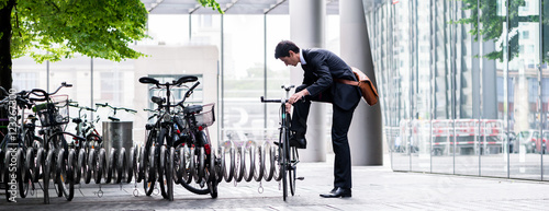 Photo Businessman parking his bicycle in town