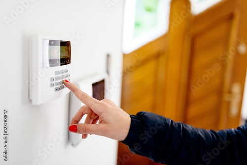 Photo Young woman entering security code on keypad