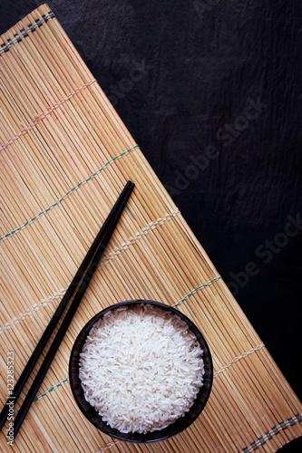 Photo  Rice and chopsticks on black background