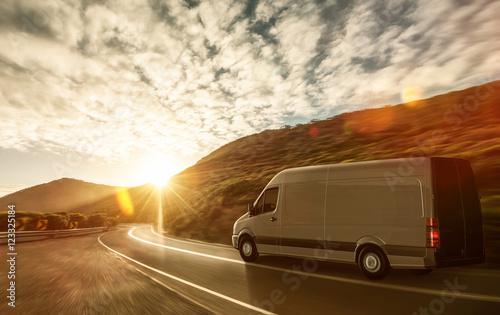 Fototapeta Lieferwagen auf Landstraße im Sonnenuntergang obraz