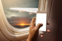 Asian Man Hand Holding Blank Screen Smart-phone On Board Of Airplane Near Window Seat And Wing