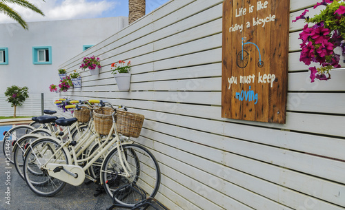 Deurstickers Fiets vintage bicycle in the parking lot near a wooden wall with flowers