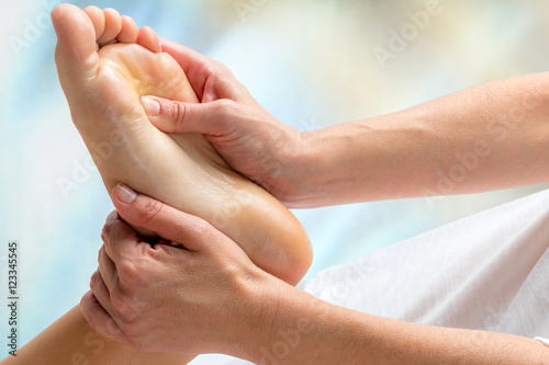 Tuinposter Pedicure Reflexologist doing treatment on foot.