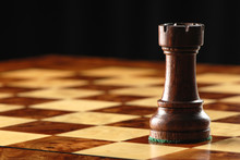 Carved Wooden Black Rook Castle Chess Piece On Elegant Maple Chessboard With Dramatic Shadowy Dark Background
