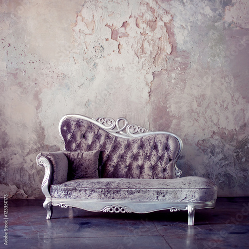 Foto-Tapete - Grunge Styled Interior. Beautiful sofa in classical style on a background of textured walls. Purple toning (von Ulia Koltyrina)