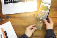 Cashier Hand Holding A Credit Card Over EDC Machine Or Credit Card Terminal With Calculator And Glasses. A Credit Card Over Japanese Bank Notes.