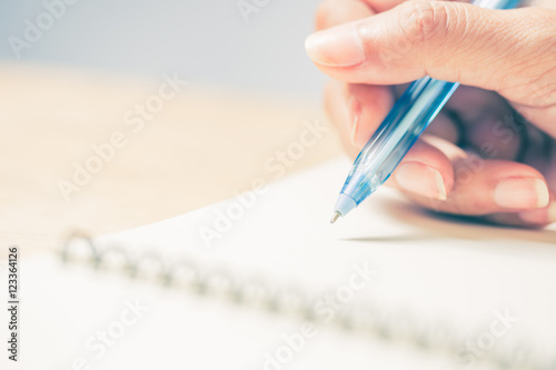 Fotografía  Business women hands working writing notebook on wooden desk, lighing effect