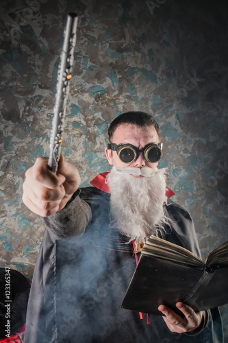 Photo  evil wizard Merlin conjures and casts a spell, raising his wand, a young man dre
