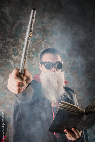 evil wizard Merlin conjures and casts a spell, raising his wand, a young man dre Wallpaper Mural