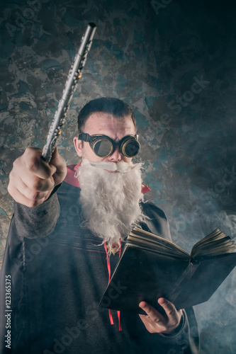 evil wizard Merlin conjures and casts a spell, raising his wand, a young man dre Canvas Print