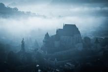 Mysterious Misty Morning Over Biertan Village, Transylvania, Romania. Blue Colors. Spooky, Halloween Concept
