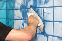 Man Applying Blue Grout To Whi...