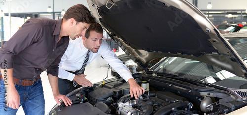 Spoed Foto op Canvas Zeilen Verkaufsgespräch in einem Autohaus - Kunde mit Verkäufer unterhalten sich über Technik eines Fahrzeuges