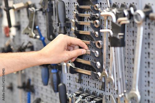 Hand eines Mechanikers greift nach Werkzeug zur Reparatur